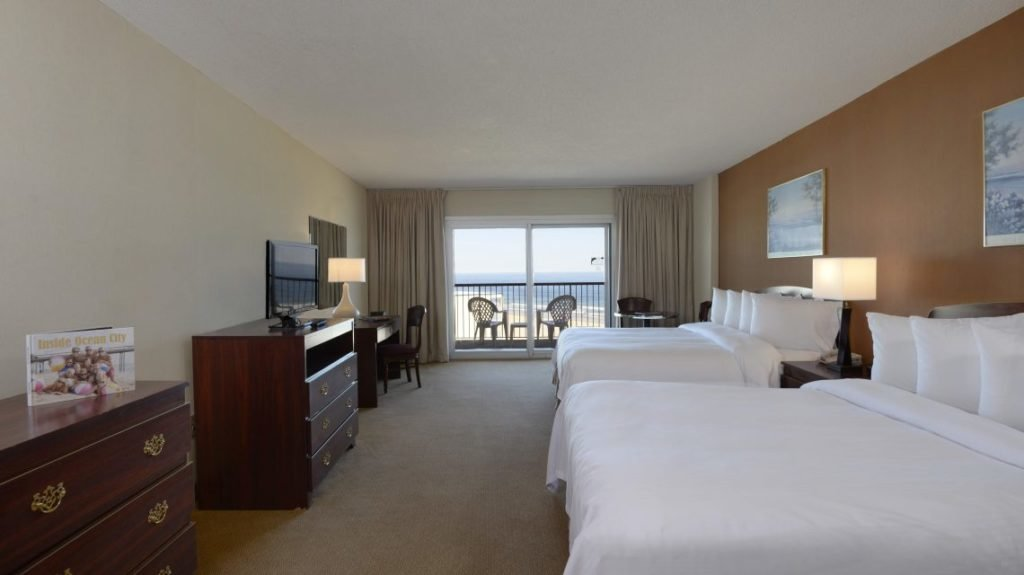 room with two king beds, tv, dresser, desk and balcony view