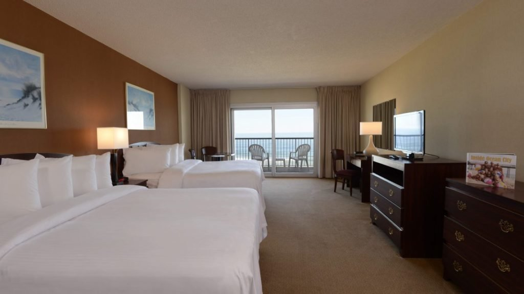 hotel room with two beds, dressers, tv and balcony view
