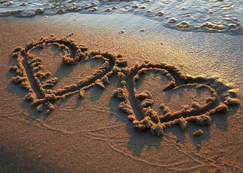 two hearts drawn in sand
