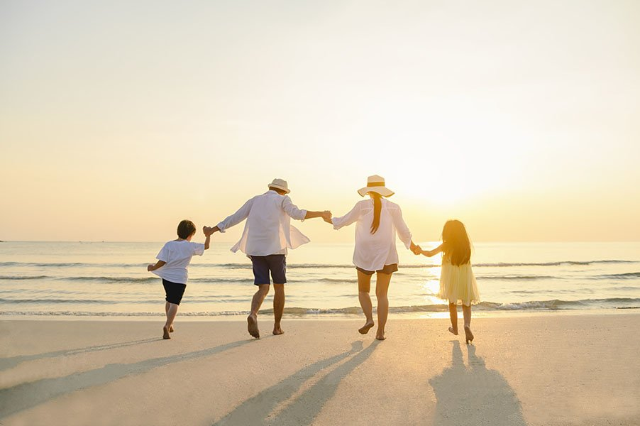 family of four holding hands and walking near beach waves