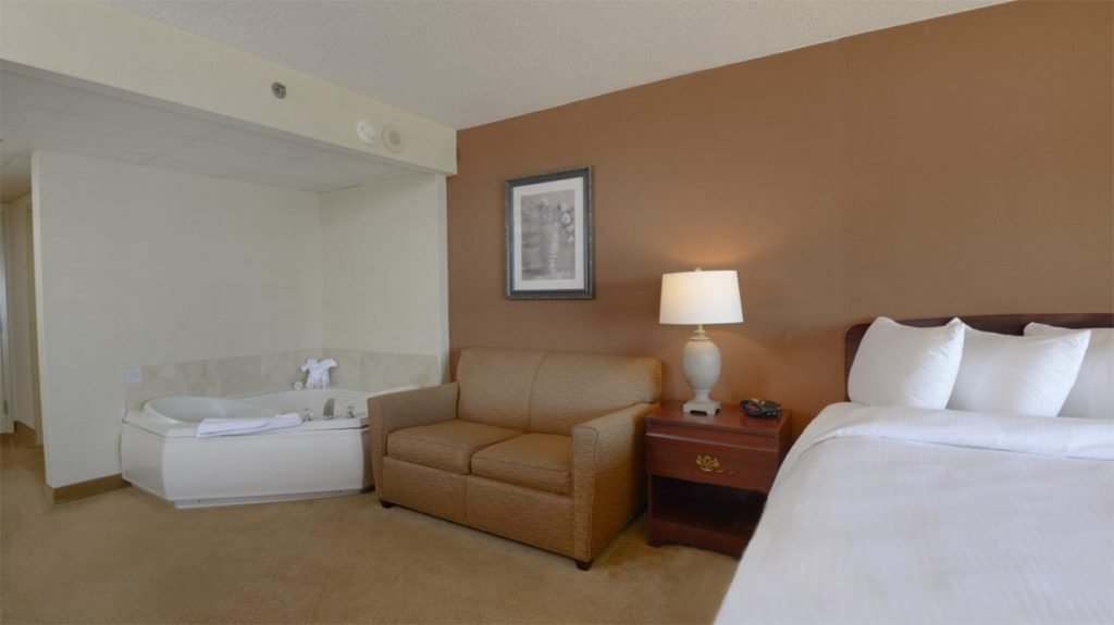 hotel room with bed sofa table and jacuzzi tub