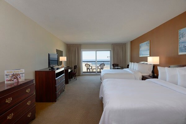 hotel room with two queen beds dressers and oceanfront balcony