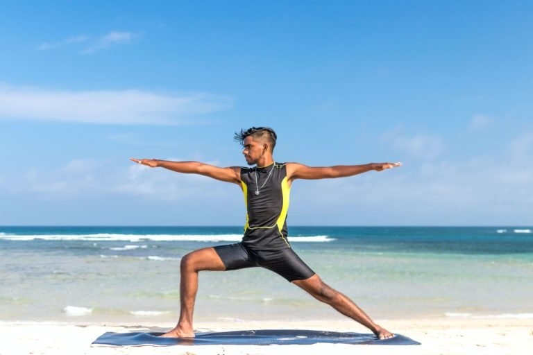 male on beach doing yoga with ocean behind him