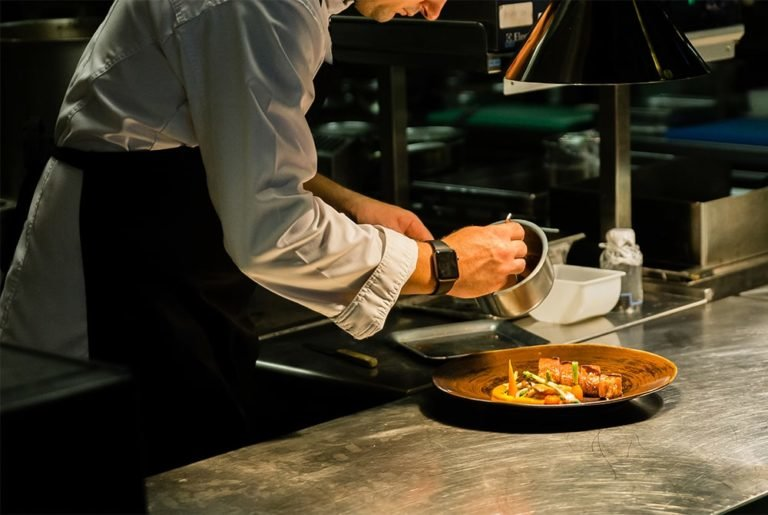 chef pouring sauce on dish in kitchen