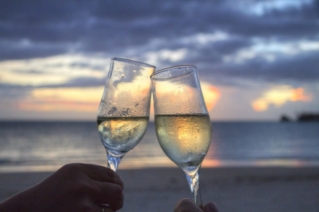champagne glass clinking in front of ocean sunset