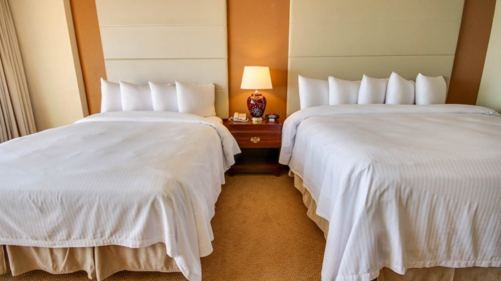 hotel room with two queen beds table and lamp