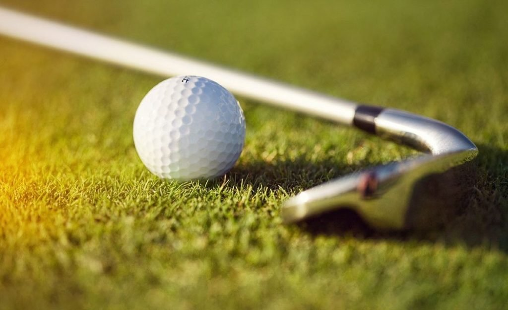 close up of golf club and ball on green