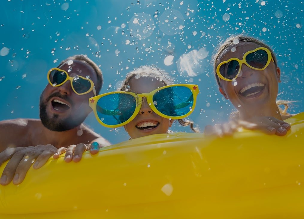 image of mom and dad with daughter in the middle wearing yellow sunglasses