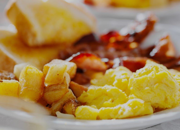 close up of breakfast plate with eggs, potatoes and bacon