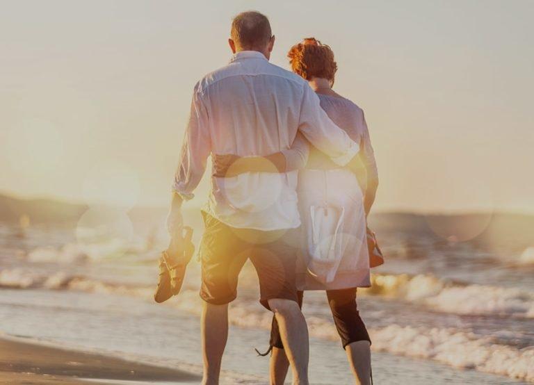 older couple walking on the beach barefoot