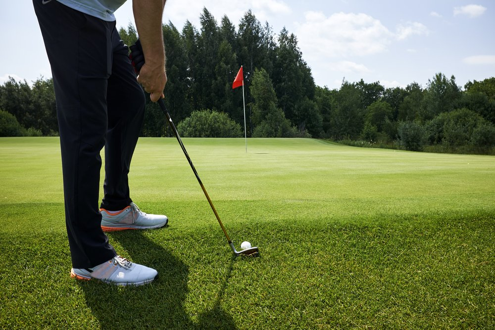 man playing golf ready to putt