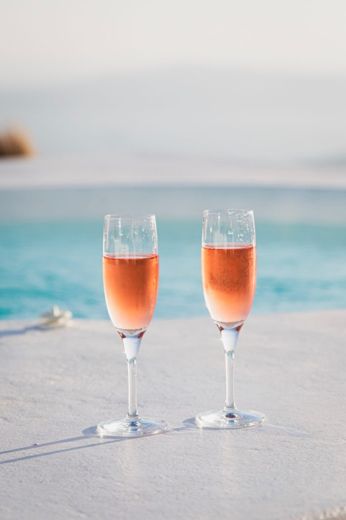 two champagne glasses by pool