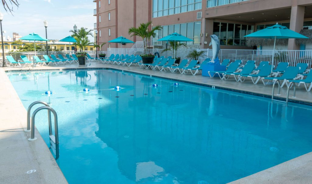 outdoor pool with blue lounge chairs and umbrellas