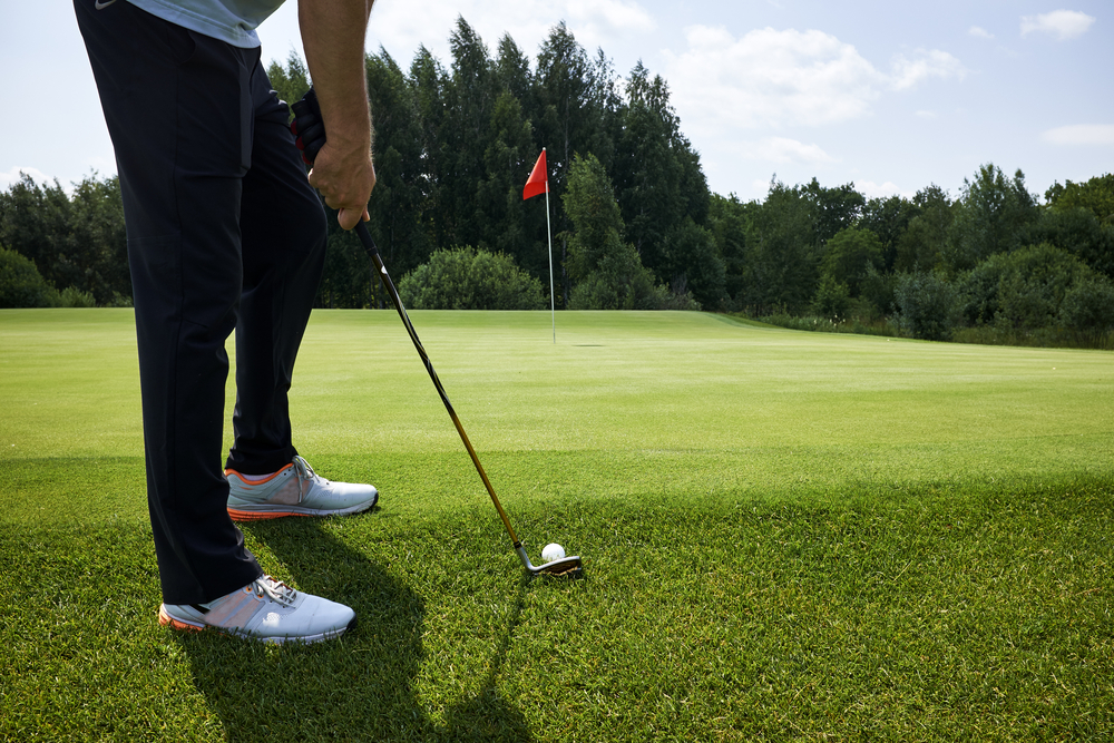 close up of golfer holding golf club by green