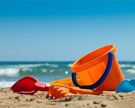 bucket and shovels on beach by ocean
