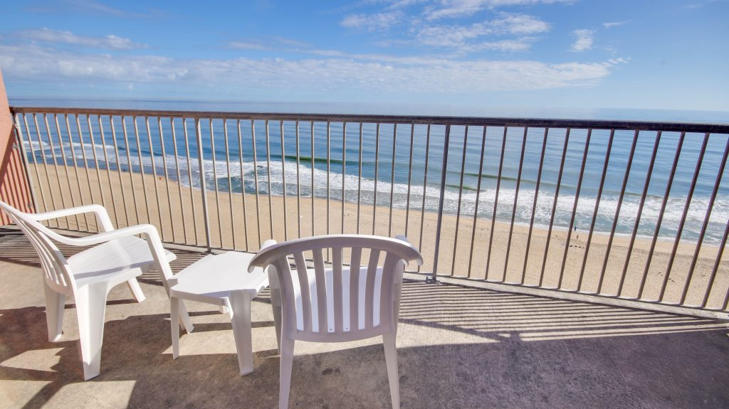 oceanfront view from deck with chairs and table