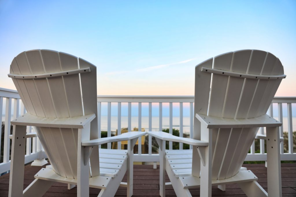 Adirondack chairs on a balcony facing the ocean
